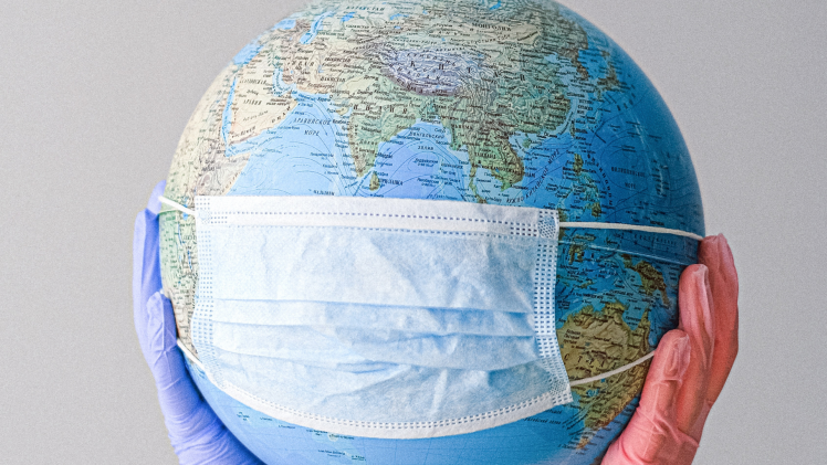 Stock Photo: Hands With Latex Gloves Holding a Globe with a Face Mask.