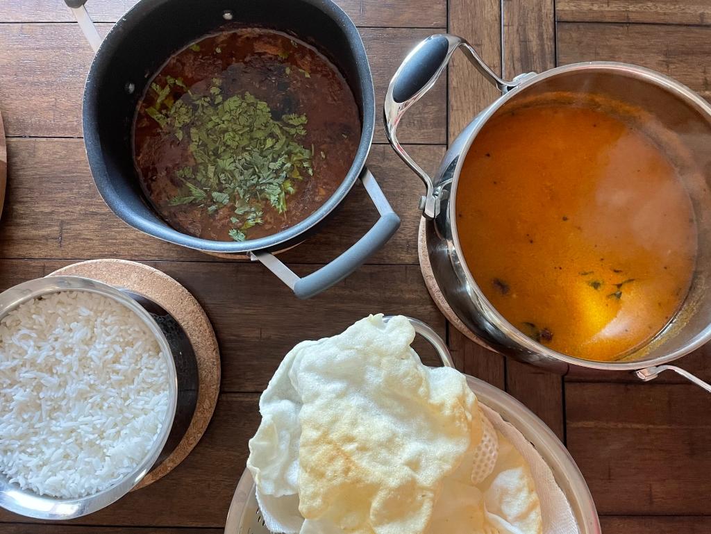 Photo featuring South Indian dishes sambar, rasam, rice, and appalam.
